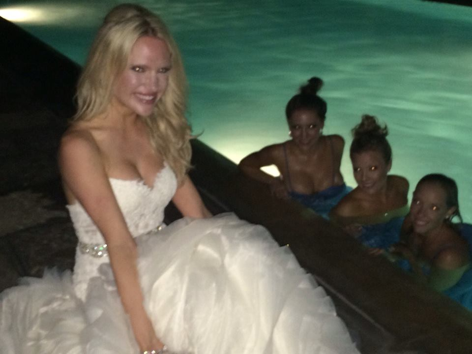 bride in Lazaro wedding dress, bridesmaids in the pool