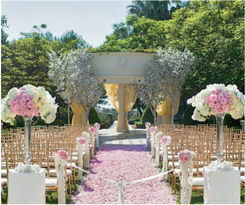 St Regis wedding venue with trees at alter and white and pink flowers at ceremony entrance