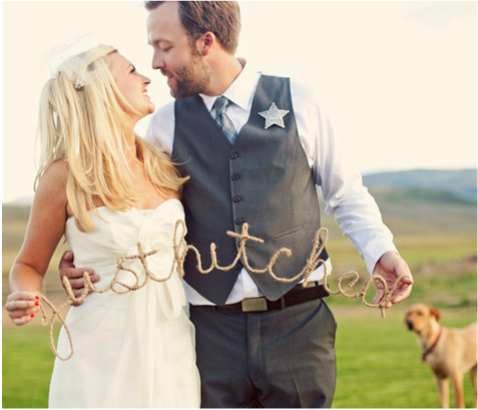 bride and groom holding just hitched sign