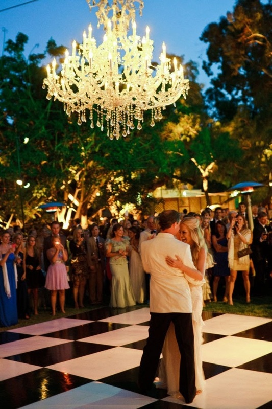 bride and groom dancing outside on checkered dance floor under chandelier