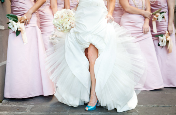 Bride showing her something blue wedding shoes and pink bridesmaid dresses