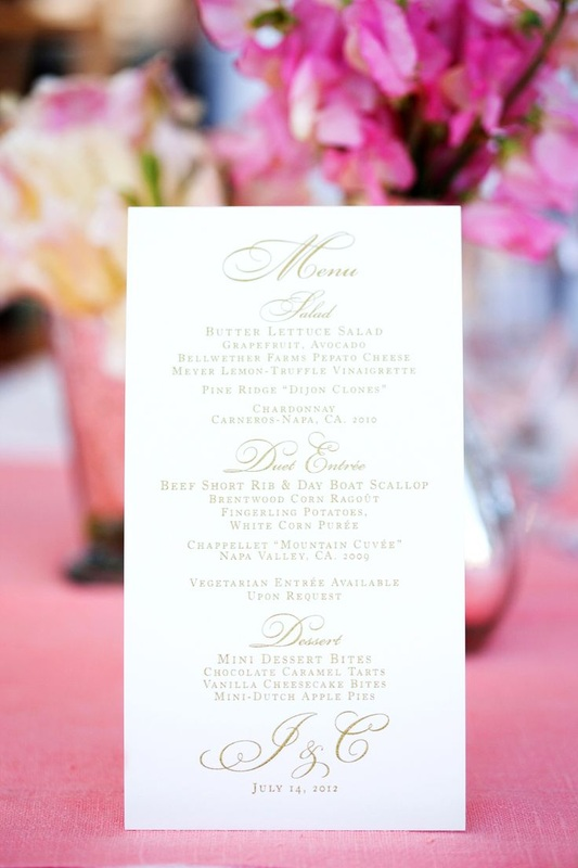wedding menu with pink linens and flowers in background