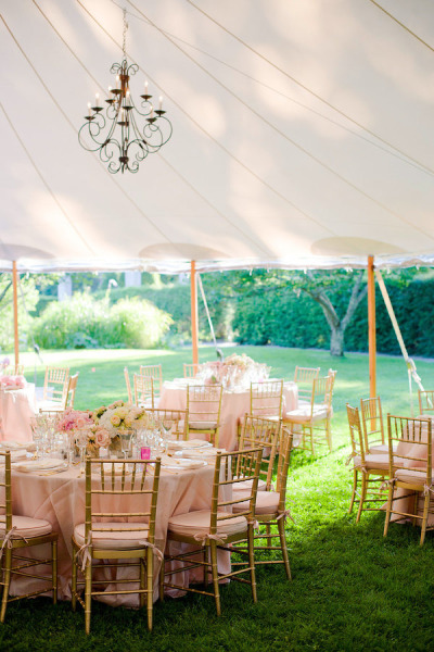 light pink reception tables with gold chairs under marquee tent