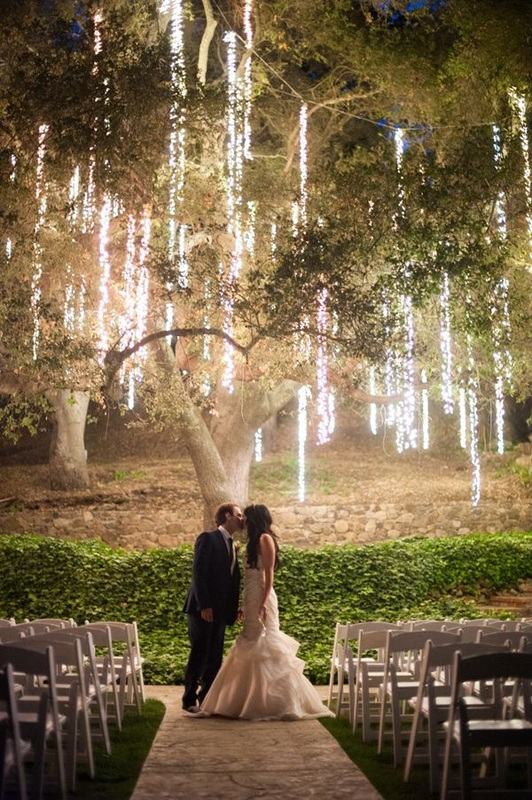 bride and groom kissing under lighted tree with Christmas lights