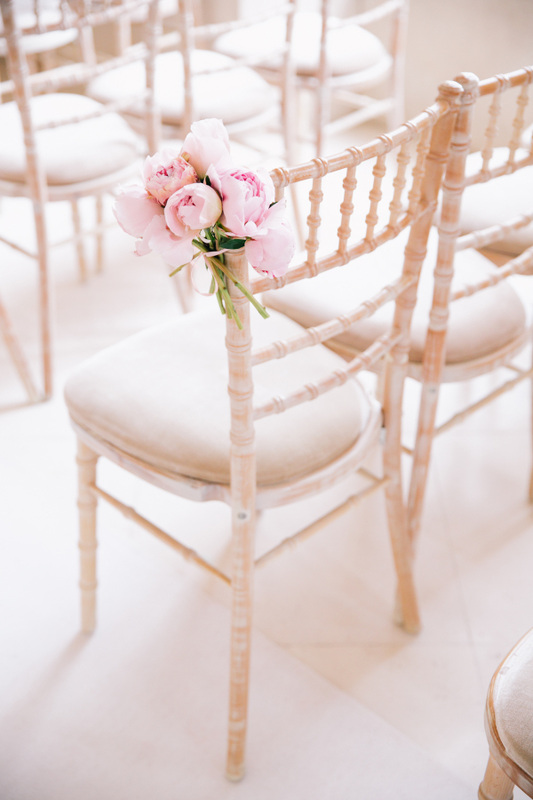 pink peonies ties to white wedding ceremony chairs
