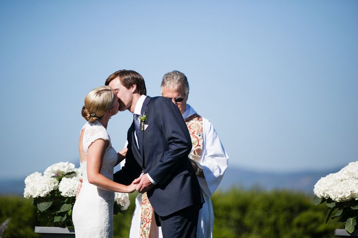 bride and groom kiss at outdoor ceremony