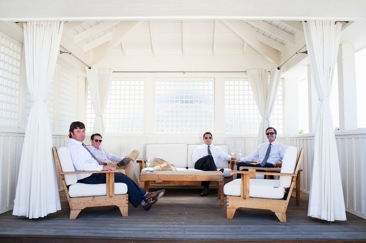 groom and guests relaxing in white room and chairs