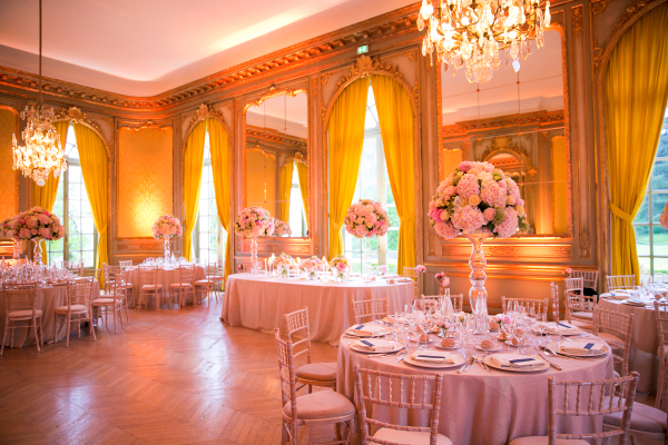 beautiful wedding reception hall with large flower bouquets and grey linens