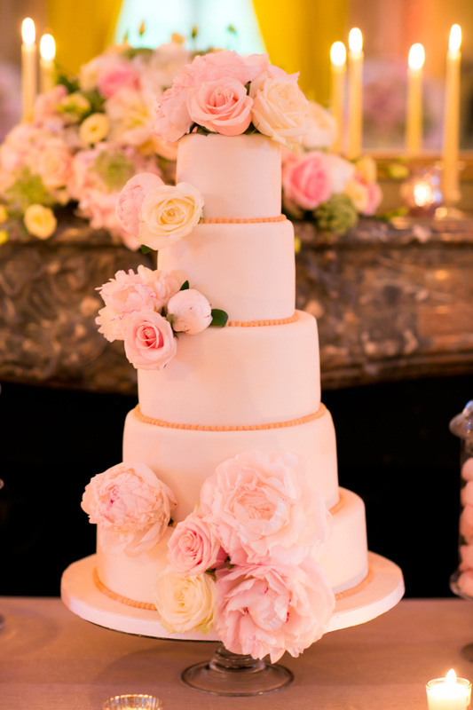 white wedding cake with pink peonies and roses