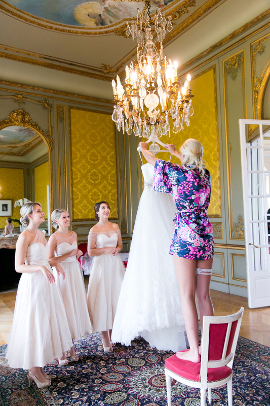 bride holding dress under chandelier at french chateau