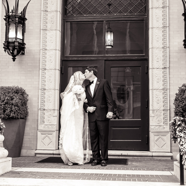 bride and groom kissing outside chapel