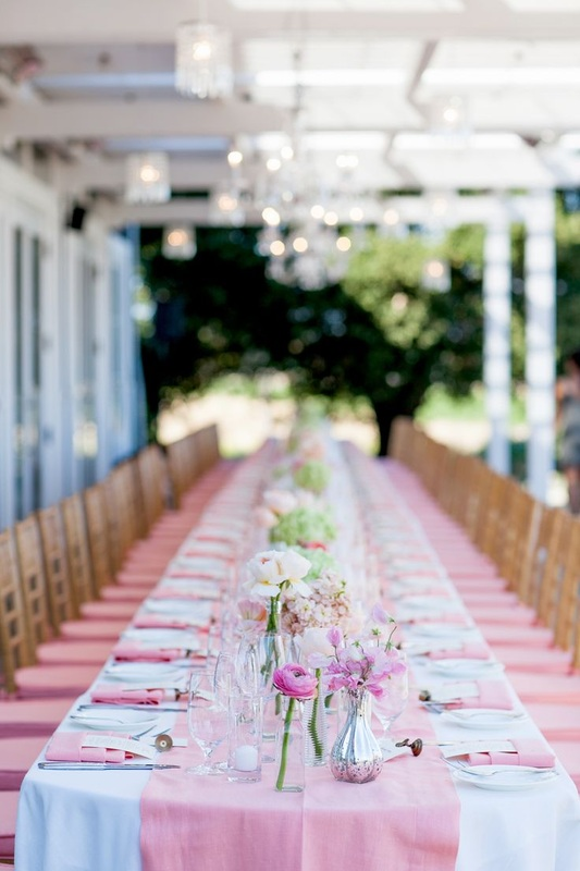 outdoor reception table set up under terrace with pink linens and white and pink flowers