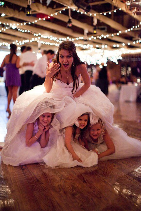 kids hiding under brides wedding dress