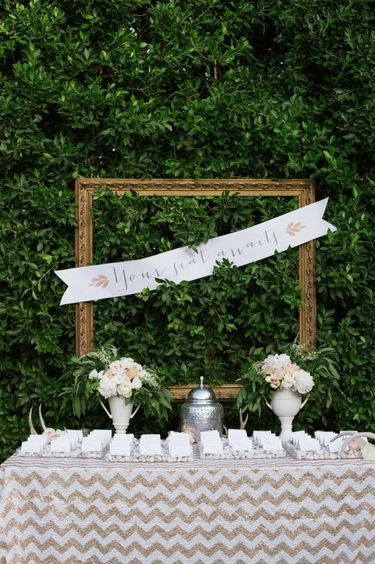 cake table with hedges and large gold frame