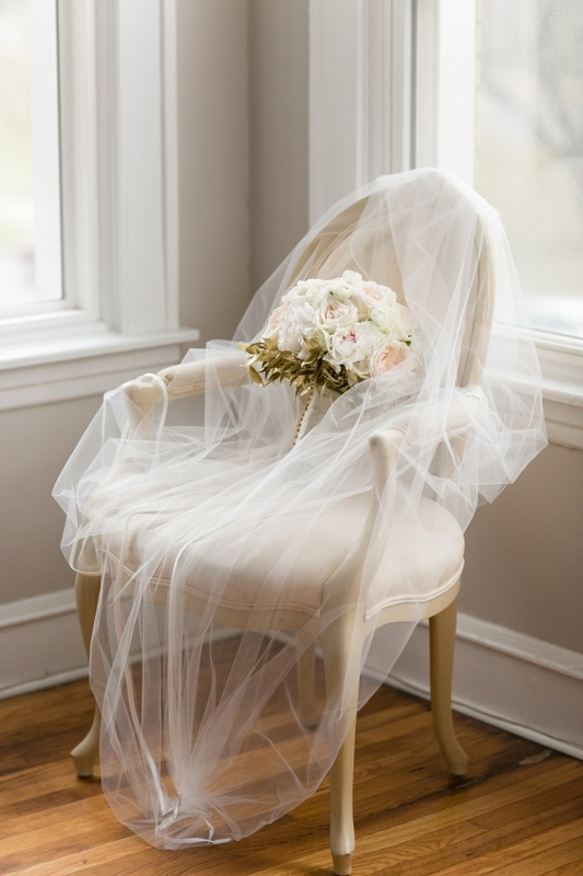 veil and brides bouquet sitting on chair