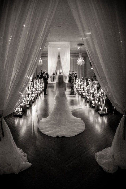 stunning aisle with candles and tall curtins