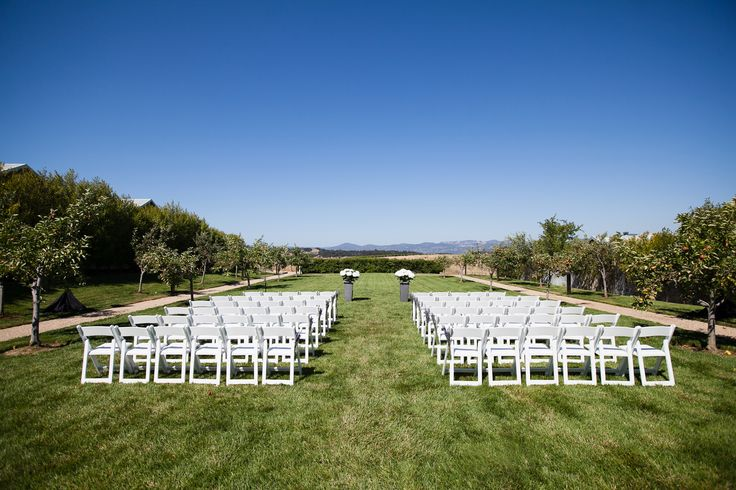 white chairs and hydrangeas overlooking vineyard ceremony site