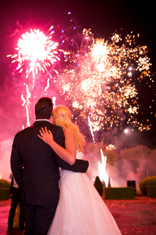 bride and groom watching fireworks during reception