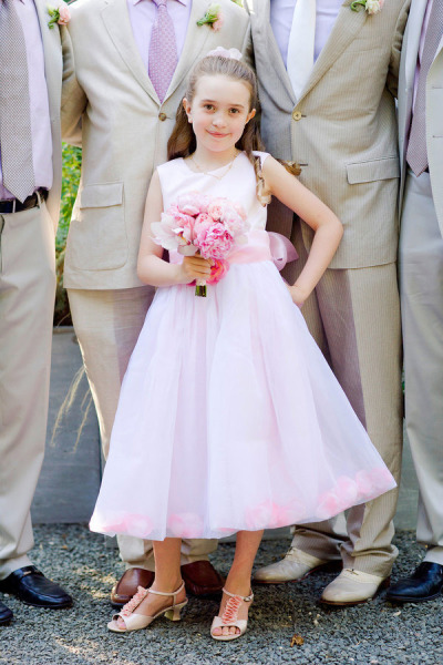 flower girl with groomsmen in the background