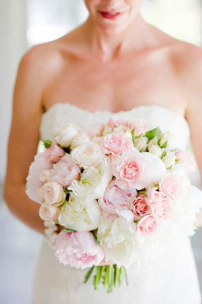 bride holding white and blush bridal bouquet