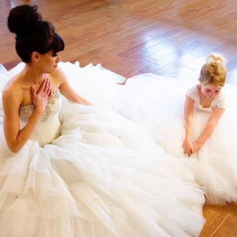 bride and flower girl sitting in ballgown wedding dress