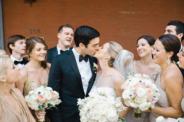 bride and groom kissing surrounded by their bridesmaids and groomsmen