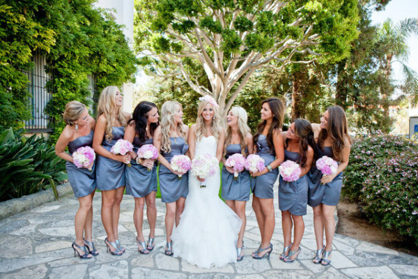 Bridesmaids in short blue dresses looking at bride in mermaid wedding dress and pink hair piece
