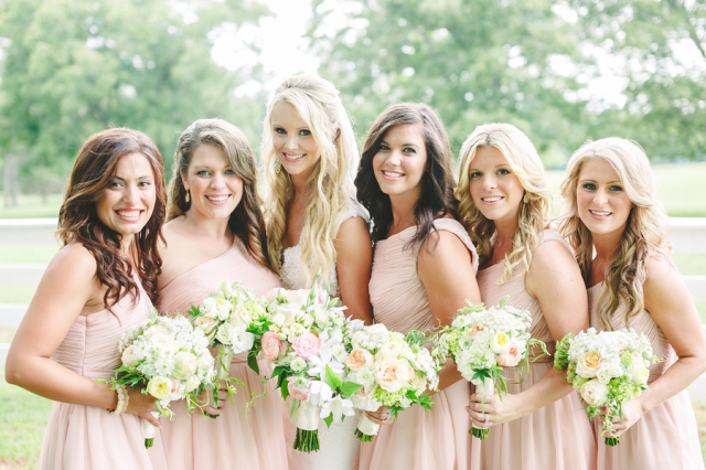 bride with bridesmaids in pick dresses and white flowers