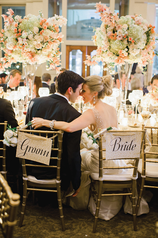 couple looking at each other in their reception chairs, black tie wedding with breathtaking flowers