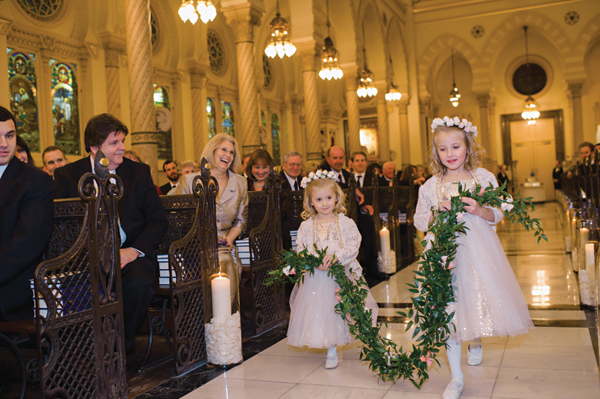 flower girls with flower crowns and a floral wreath walking down the aisle