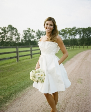 bride holding white bouquet on riding pathway