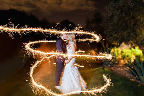 sparklers surrounding bride and groom kissing