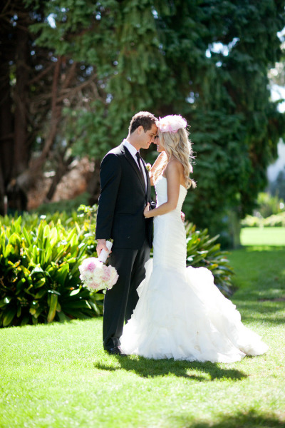 bride and groom facing each other with their noses touching. Bride wearing mermaid wedding dress and hair piece