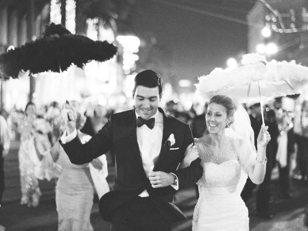 bride and groom walking to reception hall with white and black parasols