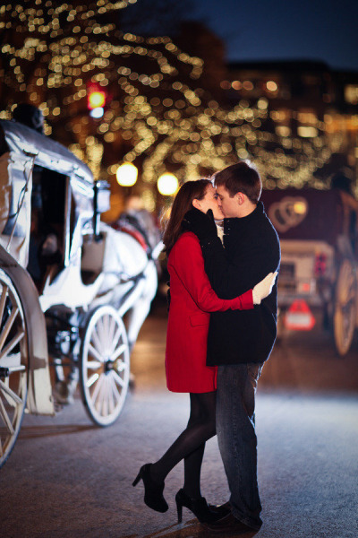 couple kissing in the winter with a carriage in the background