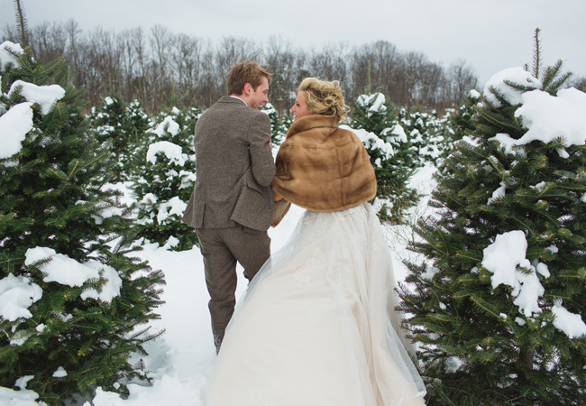 bride in fur shawl and groom in between snowy evergreen