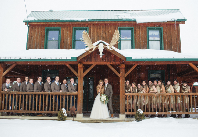 bride and groom and wedding partyy outside of cabin in the snow