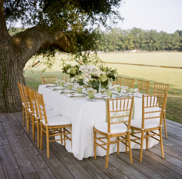styled white and green table with chivarier chairs and white bouquets