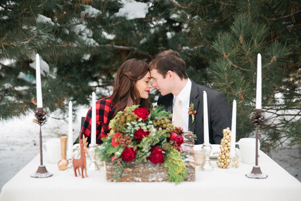 Christmas wedding shoot, bride and groom sitting at a table in the snow