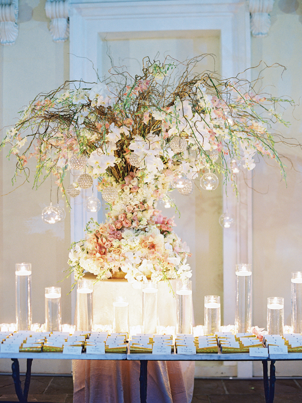 absolutely stunning floral bouquet with orchids, roses ad other white pink, orange and green flowers on the escort card table with hanging tealights