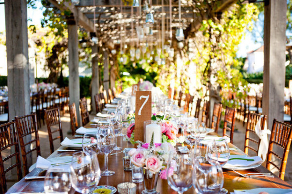 rustic kings table under vineyard vines and hanging candles