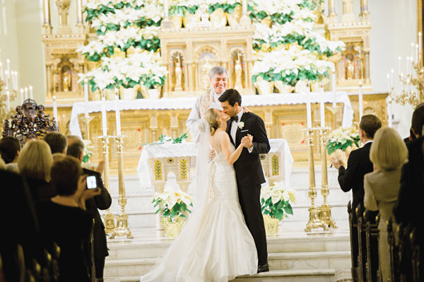 bride and groom kiss in a cathedral
