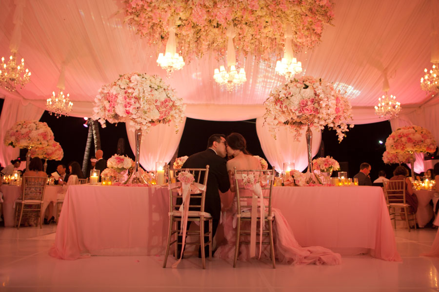 back of bride and grooms chairs decorated with flowers and ribbon: the couple kissing