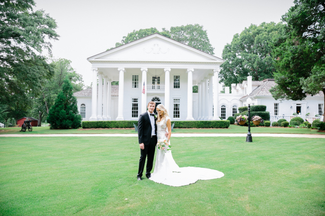 elegant and preppy bride and groom with white estate in background