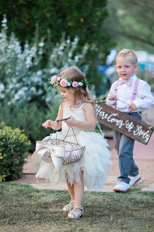 flower girl with flower halo and ring barrier carrying here comes the bride sign
