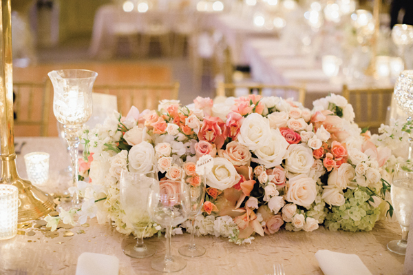 elaborate wedding floral low centerpiece with white, pink, orange and green roses and hydrangeas