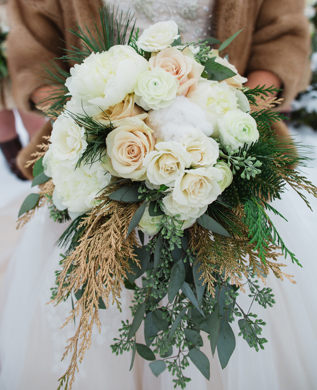 bride holding white bouquet with evergreen