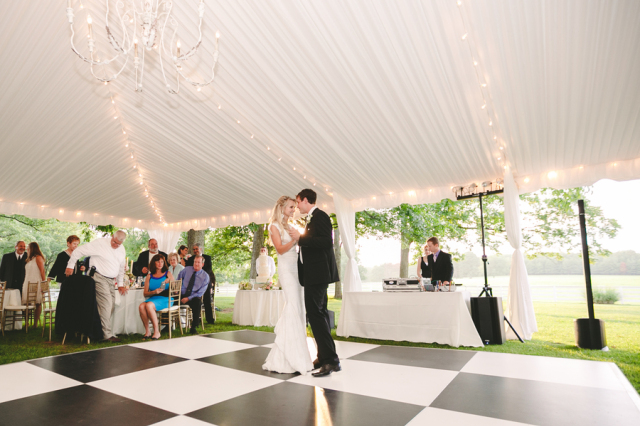 bride and groom dancing under marquee tent and checkered floor