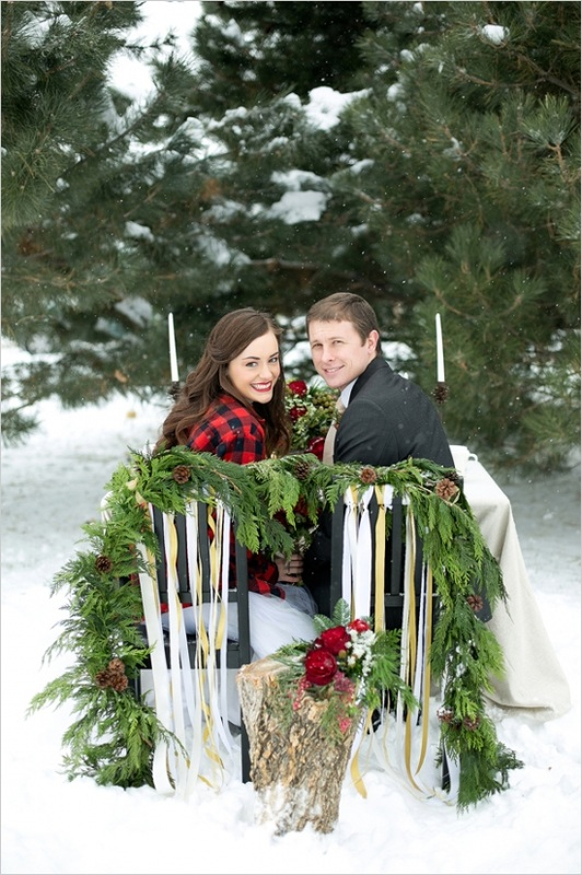 bride and groom sitting at sweetheart Christmas table in the snow