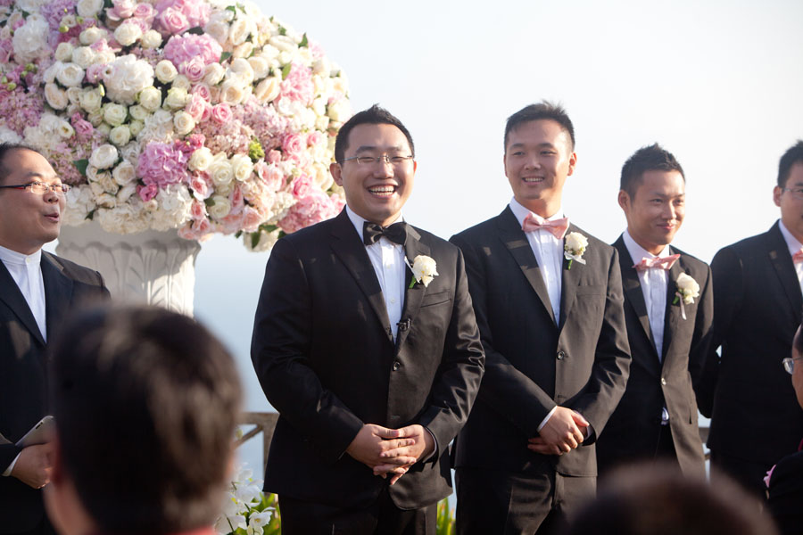 groomsmen smiling at wedding alter and huge wedding bouquet with hydrangeas and roses